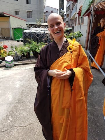 A Buddhist nun wearing Chinese robes smiles