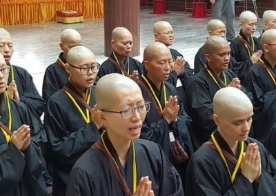 Rows of Buddhist nuns chanting with hands folded