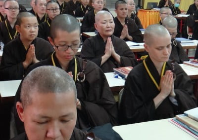 Rows of Buddhist nuns praying with hands folded