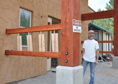 Larry shows the first stage of installing prayer wheels on either side  of the <br> front entrance to Chenrezig Hall.