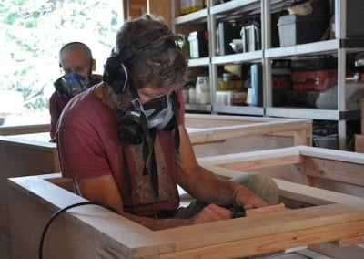 Brian and Venerable Semkye team up to sand and put urethane on the altars and planter boxes for Chenrezig Hall.