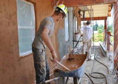 Despite our technological age, many construction skills require simple tools like wheelbarrows and hoes, as seen here when putting stucco on the outside walls.