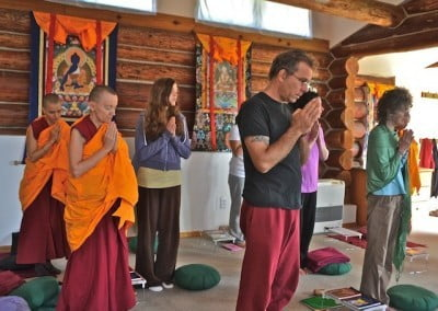 The retreatants stand and await Venerable Chodron's arrival into the meditation hall.