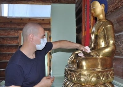 Christiaan cleans the Buddha in preparation for the teachings.