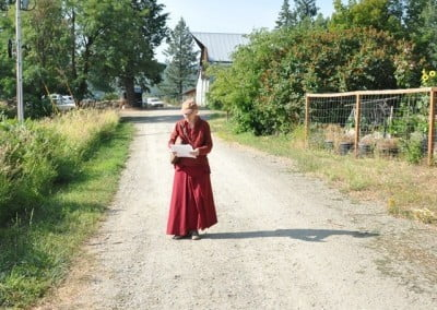 Venerable Thubten Samten studies a new chant as she waits to help guests with parking.