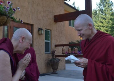 Ven. Palmo welcomes the new monk, Ven. Losang, with a bow and an offering.