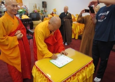 The Acharya, Ven. Chuang Wei, waits his turn to sign the ordination certificate.