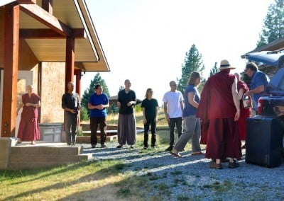 The Abbey community greets Ven. Losang and lines up to unload Sue's food offering.