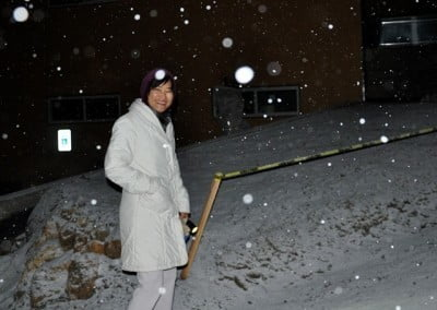 Kuni, walking through the snow to the evening session, smiles for the camera amidst the snowflakes.