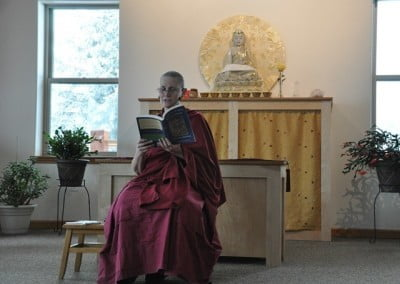 Venerable Chonyi sits in front of the Buddha and reads from a book as part of the daily BBC talk to the retreatants.