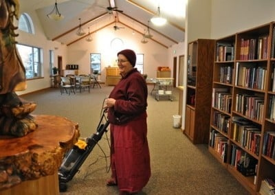 Venerable Jigme stops vacuuming for a moment to say hello to the Kuan Yin that welcomes folks to the dining room.