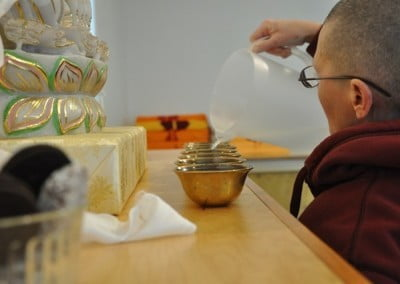 Venerable Chonyi takes some time to set up the water bowls in the dining room.