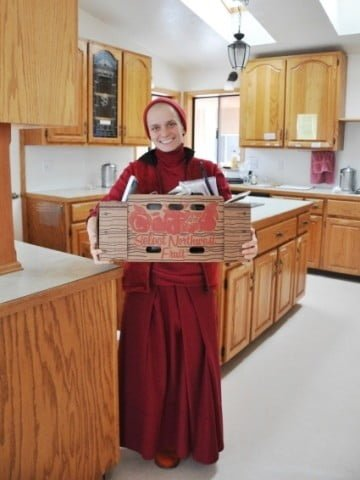 Venerable Jampa takes one of the last boxes from  the now empty old Abbey kitchen to Chenrezig Hall.