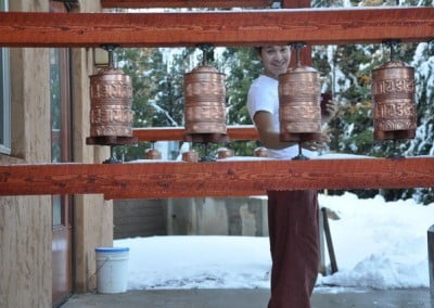 Nicolas enjoys turning the prayer wheels at the entrance to Chenrezig Hall during the break times.