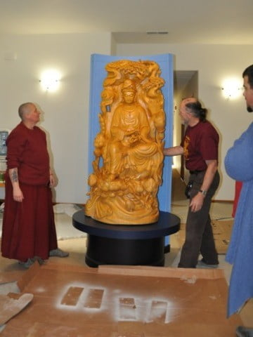 Monastics and guests look at the Kuan Yin statue to make sure it is positioned just right.