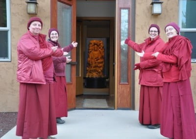 Abbey monastics line the front door of Chenrezig Hall on both sides, inside which you can see a statue of Kuan Yin
