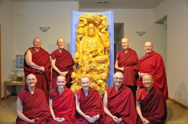 Abbey monastics pose for a photo around a statue of Kuan Yin