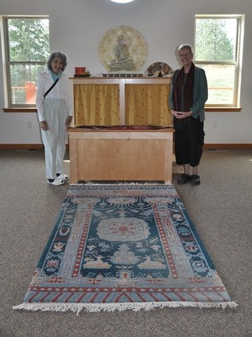 Darlene (left) offers the Abbey a  beautiful Tibetan carpet. She poses with mutual Dharma friend, Marianne.