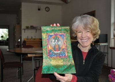 Kathleen is elated with a Chenrezig thangka offered to her by the community after a one-month stay.
