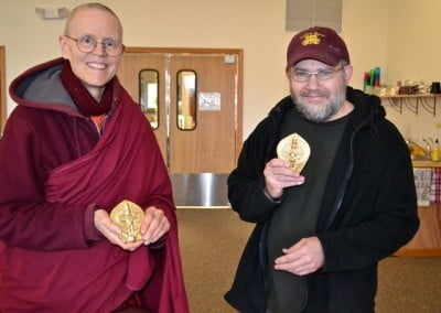 Venerable Thubten Tarpa and Shane display some of the Chenrezig tsatsas to be placed amid lights in the Chenrezig Hall chapel.