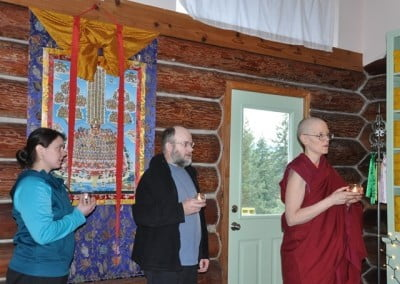 The lineage lamas look on from the thangka behind Shane and Alexis.