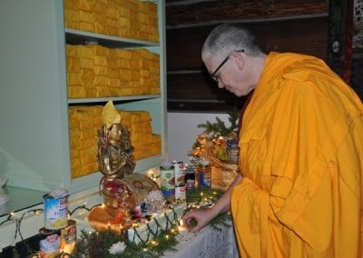 Venerable Thubten Yeshe gently places an offering of pearls from Tracy on the altar.