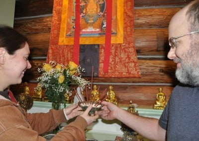Shane and Alexis offer incense to the Buddha.