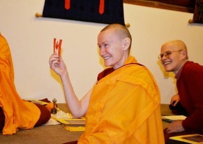 A Buddhist nun holds a paper Canadian flag