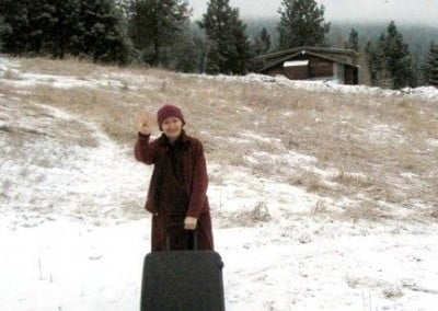 A Buddhist nun with a suitcase waves at the camera.