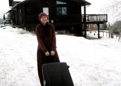 A Buddhist nun with a suitcase smiles at the camera just outside the Writing Studio