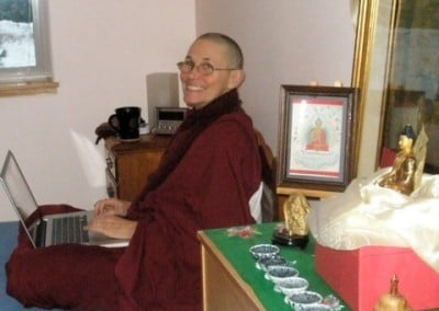 A Buddhist nun sits on a bed with a laptop computer on her lap
