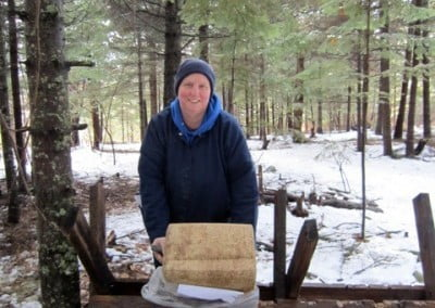 Terri uncovers a block of food for the deer and moose in the forest.