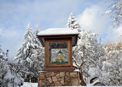 The Aspiration Buddha statue in the Buddha garden has a roof of white snow.