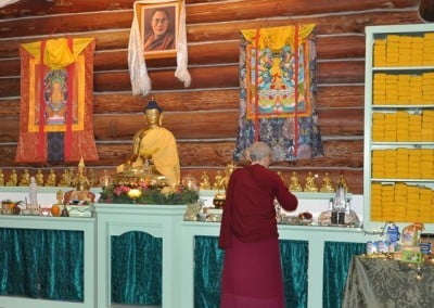 Venerable Thubten Semkye lights the remaining candles before the puja begins.