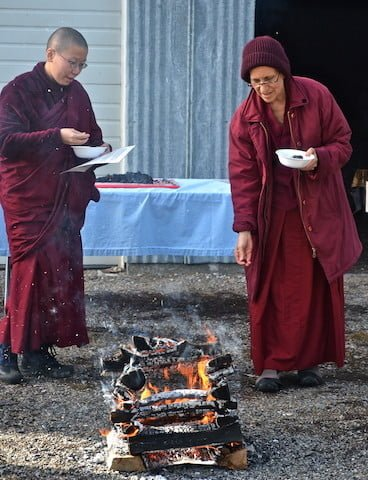 Venerable Chodron makes her offering into the fire.