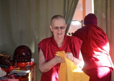 Venerable Jigme puts on her chogu while Ven. Samten looks for Venerable Chodron's arrival.