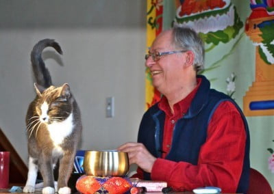 A man smiles at a cat standing on the table in front of him