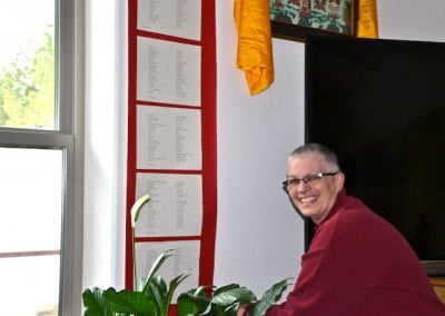 Venerable Yeshe places the prayer dedication names on the wall.