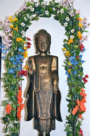 A beautiful Buddha offered by a Singaporean friend stands under a newly designed trellis of flowers.
