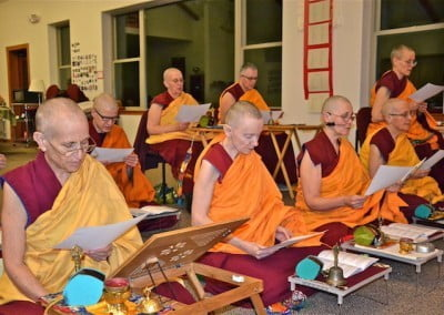Buddhist nuns seated in rows reading from lists of names