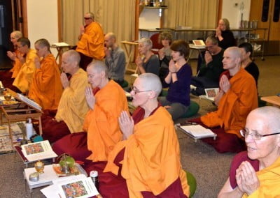 Buddhist nuns seated in rows praying