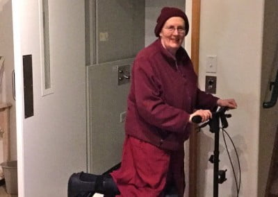 Recovering from foot surgery, Venerable Jigme travels around Chenrezig Hall on her little foot scooter.