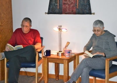 A man and woman sitting in chairs looking at books