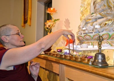 Venerable Chonyi sets up the offerings for the Guru Puja.