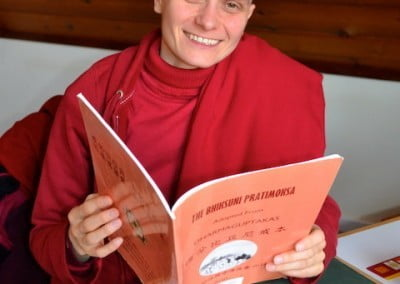 A Buddhist nun holds a book and smiles at the camera