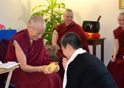 A woman bows before a Buddhist nun, who is offering her a tsa-tsa