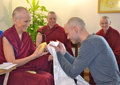 A young man offers a khata to a Buddhist nun