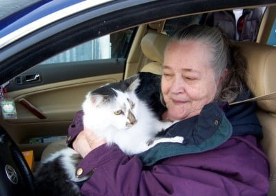 A woman seated in a car holding a cat