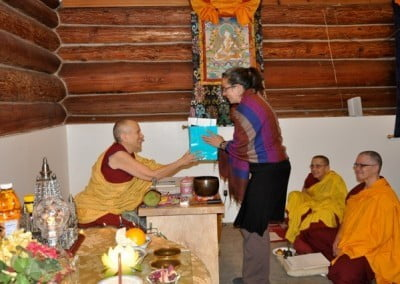 A Buddhist nun gives a gift to a lay woman