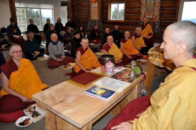 A Buddhist nun addresses a room full of listeners